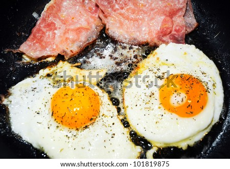close up on chicken eggs and ham slices prepared in frying pan