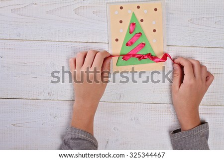Close up on child's  hands making Christmas Tree from colored paper.   Kids Art, Art Projects, Handmade New Year decorations  #325344467