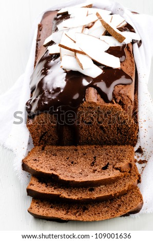 Close up on chocolate cake with chocolate frosting flowing down the side, garnished with coconut slices
