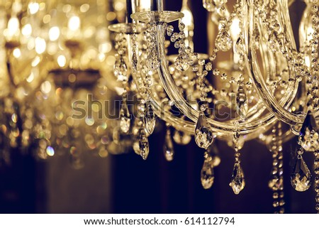 Close up on crystal of contemporary chandelier, is a branched ornamental light fixture designed to be mounted on ceilings or walls. - Shutterstock ID 614112794