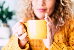 Close up on cup with tea or coffe drink inside and beautiful defocused woman in background - concept of relax and healthy lifestyle with nice people - yellow colors mood