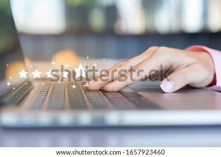 close up on customer woman hand pressing on laptop keyboard with five star rating feedback icon and press level excellent rank for giving best score point to review the service , technology business