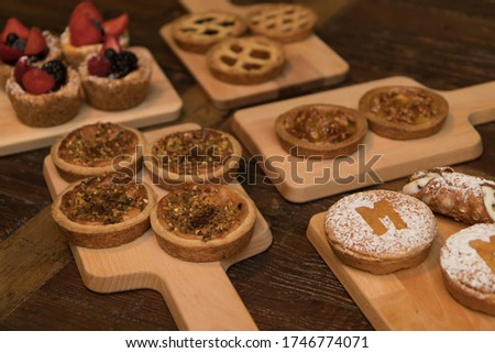Close up on delicious confectionery pastry items disposed on wooden chopping boards, no people are visible.
