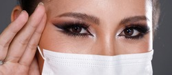 Close up on Eye make up Portrait of 20s Asian Woman black hair black turtle neck dress. Fashion Girl poses view looks, cosmetic on Eyes, wear protective face mask over gray Background isolated
