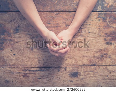 Close up on female hands folded in prayer at a wooden table - Shutterstock ID 272600858