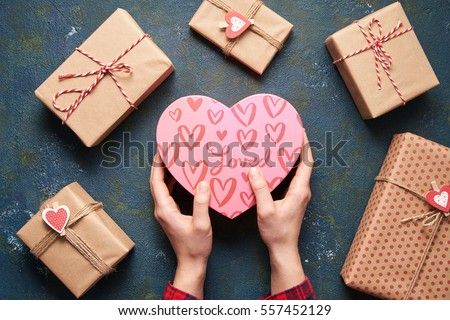 Stock Photo Close up on female hands holding a gift in a pink heart presents for valentine day, birthday, mother's day. Flat lay. Symbol of love. Valentines day background with a gift boxes on concrete board.