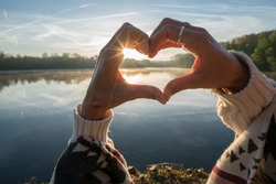 Close up on female's hands making a heart shape finger frame on lake forest landscape, sunbeam. People love nature environment concept