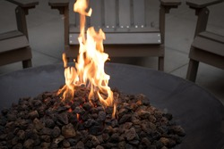 Close up on glowing lava rock coals in a black iron fire pit, with motion blurred flames, and chairs in the dark background