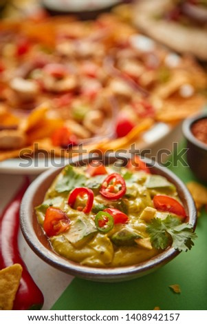 Close up on guacamole dip in ceramic bowl with various freshly made Mexican foods assortment in the back. Placed on colorful table. With nachos, tacos, tortillas, grilled meat, dips, salsa and #1408942157