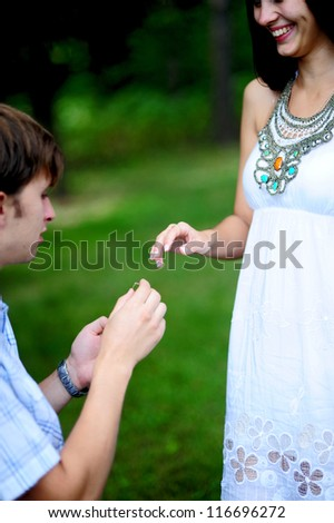 Close up on hand of a man put on an engagement ring on the finger of the bride - stock photo