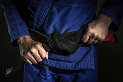 Close up on hand of unknown caucasian man holding brazilian jiu jitsu bjj black belt around his waist while wearing kimono gi in dark - martial arts mastery skill and confidence achievement concept
