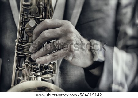 Close up on hand playing saxophone in a blurry and grungy old style photograph