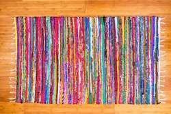 Close up on hand woven rug with red, blue, yellow, purple and other colors over bamboo floor as frame
