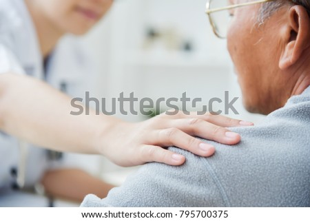 Close up on hand. Young Asian Female doctor comforting senior male patient in medical office.