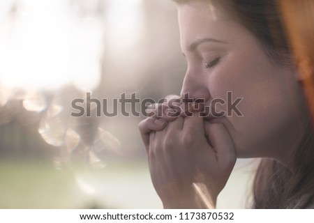 Close-up on hands and face of sad young woman with anxiety against blurred background