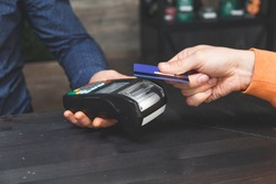 Close-up on hands. Man paying for order with credit card NFC technology using bank terminal