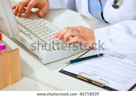 Close-up on hands of female medical doctor woman working at table