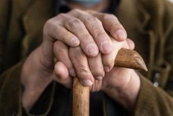 Close up on hands of unknown old caucasian man pensioner senior holding cane walking stick while sitting and waiting - real people old age senility concept copy space
