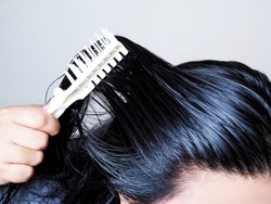 Close-up on head of Asian people have long black hair, combing hair with hairbrush. Black and thick hair health.