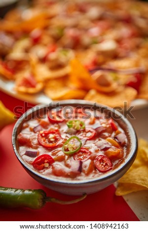 Close up on hot tomato dip in ceramic bowl with various freshly made Mexican foods assortment in the back. Placed on colorful table. With nachos, tacos, tortillas, grilled meat, dips, salsa and #1408942163
