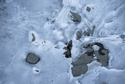close up on lake bank rocks surrounded with cold frozen ice plaques on groundfloor