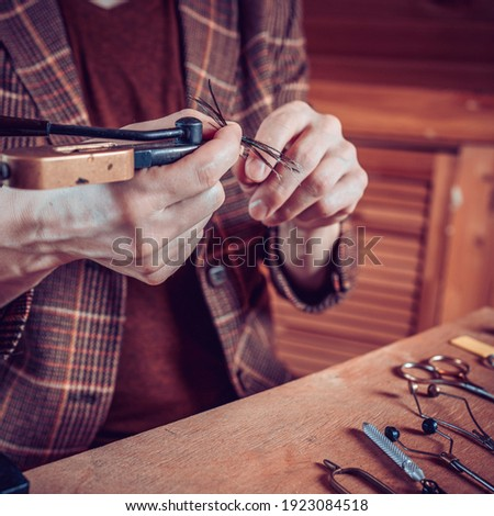 Close up on man's hands tying a fly for fishing Stock fotó ©