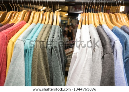 Close up on many of colorful shirts on the cloth hangers and rails with blurred people behind through the cloths as background. Summer, street store, merchant, shopping and discount store concept.