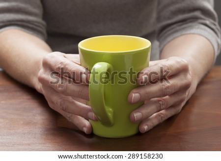 close-up on mature woman's hands thinking and relaxing at breaks with a green cup of coffee or tea #289158230