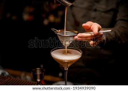 close-up on metal sieve through which male bartender pours frothy espresso martini cocktail into glass Stockfoto ©