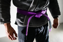 Close Up on Midsection Of A Brazilian Jiu JItsu BJJ fighter with purple belt in a black gi kimono