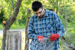 Close up on midsection of young adult caucasian man holding protective chain link diamond wire fence in the field in day with copy space