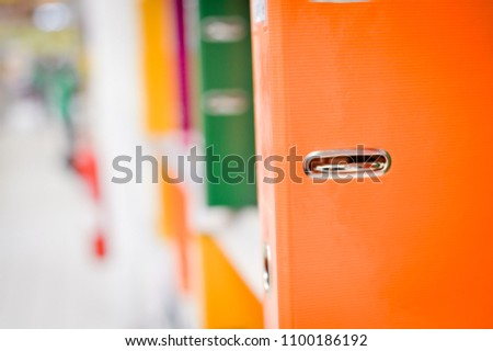 Close up on multicolored office folders on the bookshelf backgrounds. Many working stationery, stacked records. Different color spectrum documents. Educational or financial file-box object supplies #1100186192