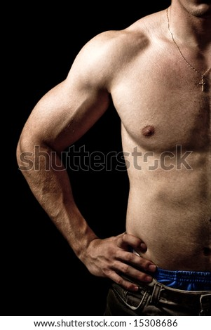 Close-up on muscular man isolated on black background