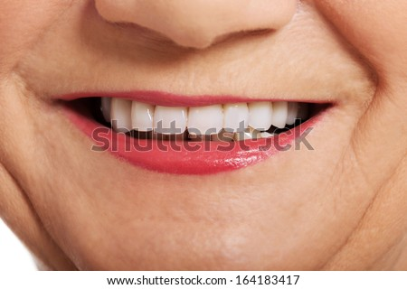Close up on ol woman\'s perfect smile, teeth. Over white.