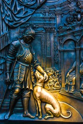 Close-up on one part of the bronze bas-relief with King Wenceslaus IV of Bohemia with his hunting dog on the pedestal of the statue of John of Nepomuk at the Charles Bridge in Prague, Czech Republic.