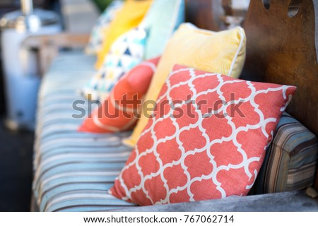 Close up on orange and yellow pattern throw pillows on an outdoor patio chair, with a blue striped cushioned bench