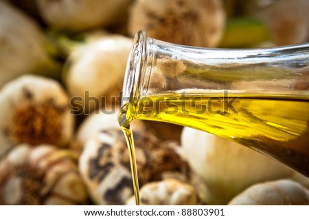 Close-up on pouring extra-virgin olive oil with fresh garlic in the background.