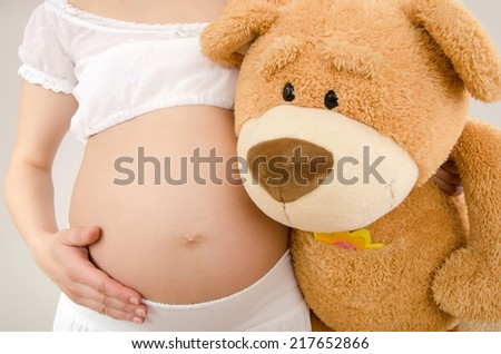 Close up on pregnant belly and a big teddy bear. Woman expecting a baby with a cute big teddy bear hugging her belly.
