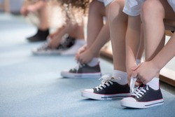 Close-up on school kids' legs while they're sitting on a bench and tying their sport shoes for physical education activities
