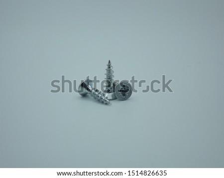 Close-up on screws, metal screws, iron screws, wood screws on white background