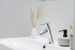 Close-up on simple silver tap in classic bathroom washbasin with decorations
