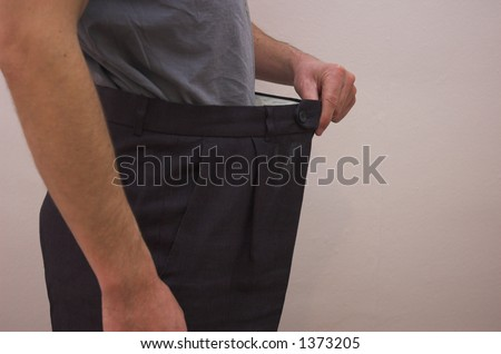 Close up on slimmed down male waistline wearing old trousers to demonstrate weight loss.