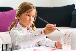 Close up on small caucasian girl painting at home - Little kid using paintbrush to finish art class for school - Back to school creativity childhood and growing up concept