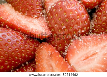 close up on some sliced strawberries covered in white sugar granules