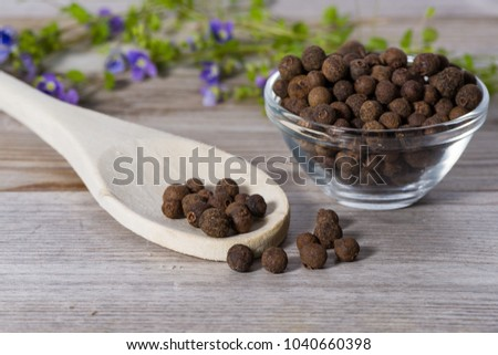 Close up on spoon with allspice (pimento) on wooden cutting board. #1040660398