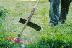Close up on string trimmer head weed cutter petrol or electric brushcutter working in the yard or field cutting grass in garden in day low angle view
