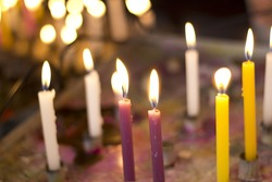 Close up on the candle of an improvised chapel's altar.