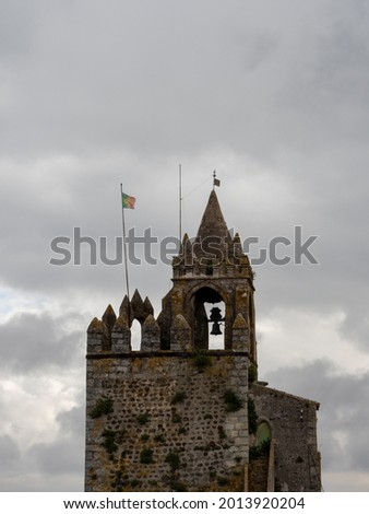 Close up on the Clock tower of the Montemor-o-Novo Castle, with the portuguese flag waving and a dramatic sky in the background. Montemor-o-Novo, Portugal. Foto stock ©