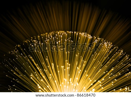 Close up on the ends of many illuminated fiber optic strands with black and yellow blur background.