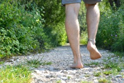 Close-up on the feet - walks across a pebble path in the woods and relaxes in the nature at summery temperatures